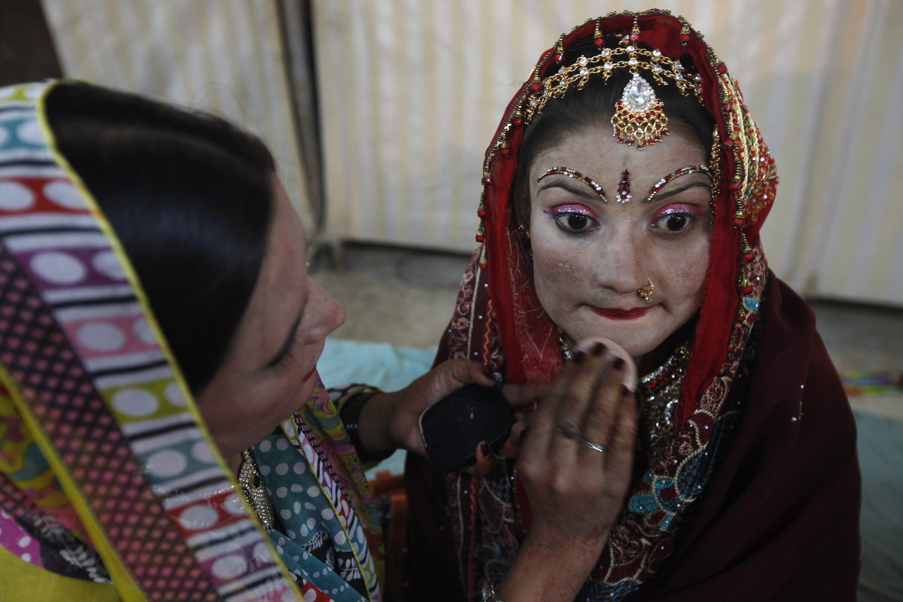 Makeup is applied on a bride's face during a mass marriage